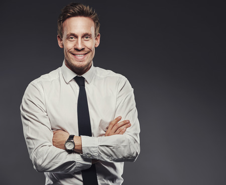 upper body: Confident happy businessman with a lovely beaming smile standing with folded arms against a grey background, upper body with copy space
