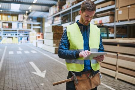 Młody pracownik hurtowni zajmujących się dostawami budowlanych stojących na dysku za pośrednictwem konsultacji podręczny komputer typu tablet