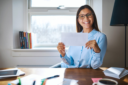 professional woman: Smiling single female in eyeglasses and blue blouse holding envelope with blank copy space while seated behind desk in home office