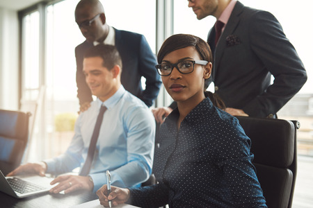 hardworking: Attractive serious businesswoman wearing eyeglasses and blue blouse sitting at conference table with three male co-workers in front of large bright window