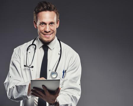 bata blanca: Doctor sonriente con el estetoscopio y la tableta llevaba bata blanca y lazo negro está parado contra un fondo oscuro