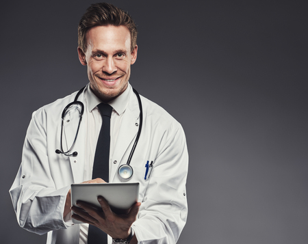 white coat: Smiling doctor with stethoscope and tablet wearing white lab coat and black tie stands against a dark background Stock Photo