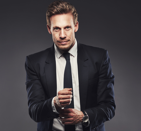upper body: Pensive attractive businessman adjusting his cuff on his shirt as he stands looking at the camera with a quiet smile, upper body on grey