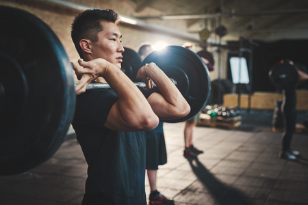 asian bodybuilder: Fit young man lifting barbells looking focused, working out in a gym with other people