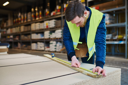 high visibility: Handyman working in warehouse measuring a piece of wood