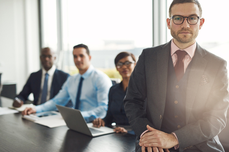 Handsome Caucasian executive with three employees sitting on edge table with back to large bright office window with light flare