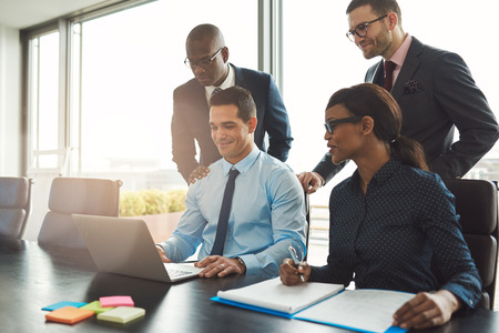 Group of happy diverse male and female business people in formal gathered around laptop computer in bright office 스톡 콘텐츠