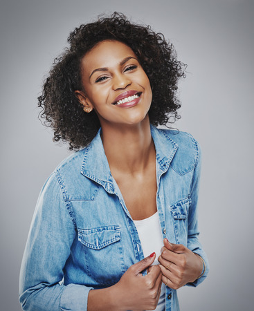 Gorgeous laughing woman with hands holding buttons of blue denim shirt centered in frame with gray background vignette