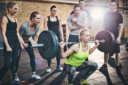 en cuclillas: Ajuste a la mujer joven de elevación pesas en busca centrado, que se resuelve en un gimnasio con otras personas animándola Foto de archivo