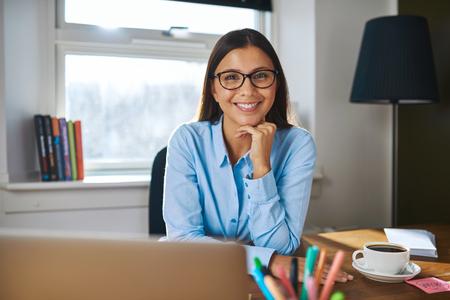trabajando en casa: Sonriendo atractivas gafas empresario hembra que usan cómodo que se sienta en su escritorio en su oficina en el hogar Foto de archivo