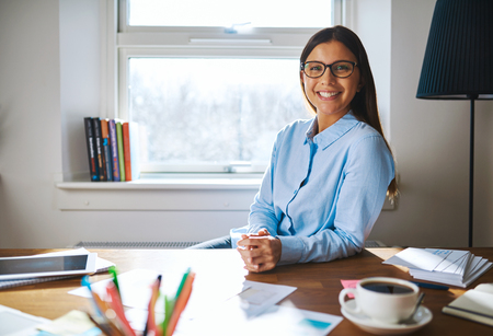 self employed: Self employed woman wearing glasses and blue shirt at desk with folded hands next to full cup of coffee and papers in home office