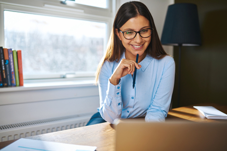 pleased: Smiling young businesswoman working at home sitting at her desk reading information on the laptop with a pleased expression