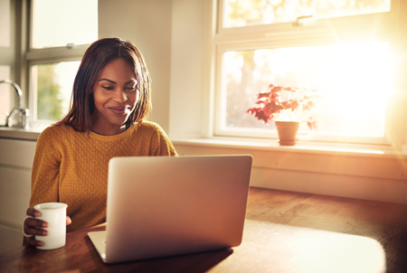 大人の女性のカップを保持しているキッチンの明るい日当たりの良い窓際に座って彼女のノート パソコンを見ながら笑っています。