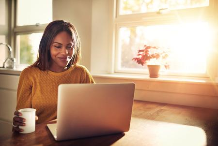 Adulto taza de explotación femenina y riendo mientras mira a su ordenador portátil mientras está sentado cerca de la ventana de sol brillante en la cocina