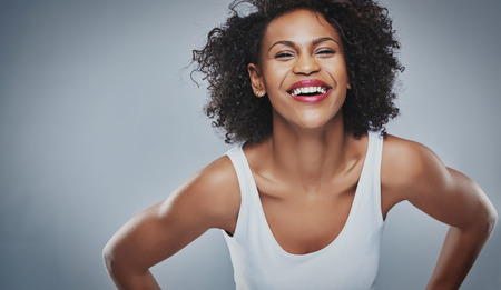 leaning forward: Single laughing young adult woman in sleeveless undershirt and soft frizzy hair leaning forward over gray background and copy space Stock Photo