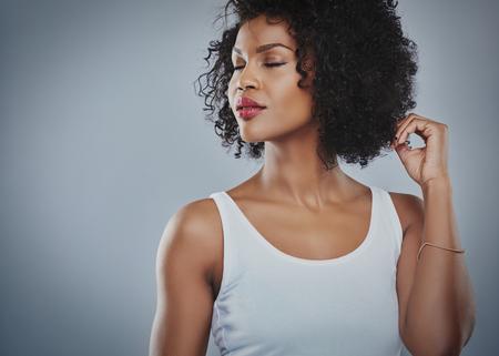 Ver recortada parte superior del cuerpo de la hermosa mujer africana joven que mira de lado con los ojos y los dedos cerrados, tocando el pelo y de la copia Foto de archivo