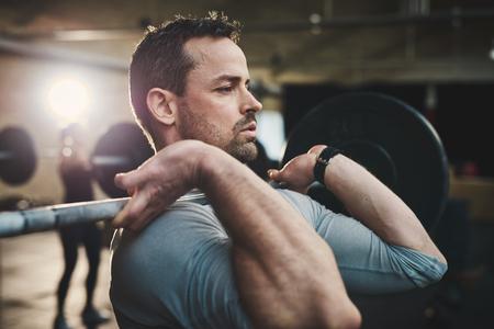 Hombre joven en forma de elevación pesas mirando enfocados, que se resuelve en un gimnasio con otras personas Foto de archivo - 57529043