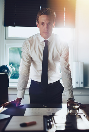 Executive business man standing at desk at office with hands resting at desk looking serious at camera