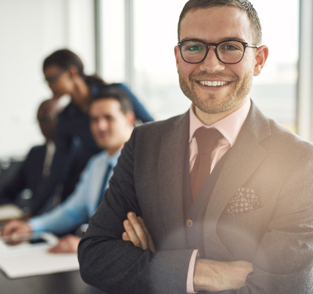 executive affable: Smiling confident businessman wearing glasses standing with folded arms looking at the camera, close up view with colleagues working behind