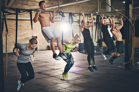 pullups: Fit young people doing pullups looking determined, working out in a gym