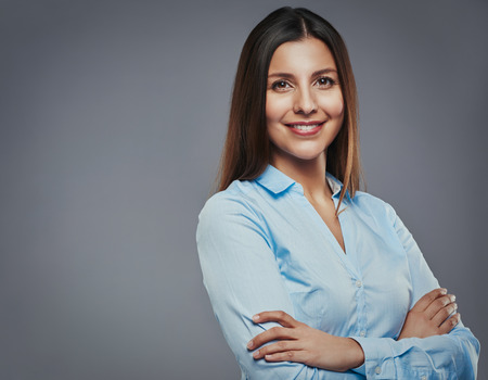 executive woman: Beautiful young businesswoman with arms crossed looking confident against a gray background
