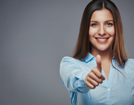 Überzeugte junge Geschäftsfrau, die Daumen nach oben vor einem grauen Hintergrund geben Standard-Bild