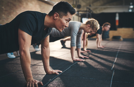 Fit young people doing pushups in a gym looking focused Stockfoto