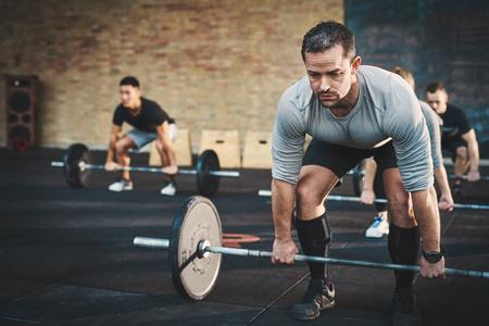Hombre joven en forma de elevación pesas mirando enfocados, que se resuelve en un gimnasio con otras personas Foto de archivo - 57531028