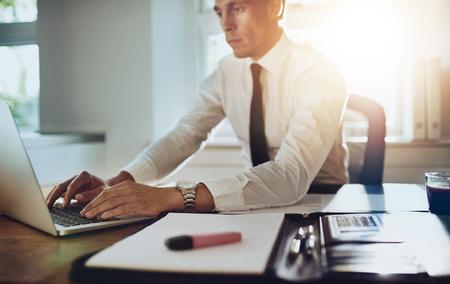 Geschäftsmann auf einem Laptop im Büro mit Dokumenten auf seinem Schreibtisch, trägt Anzug und Krawatte