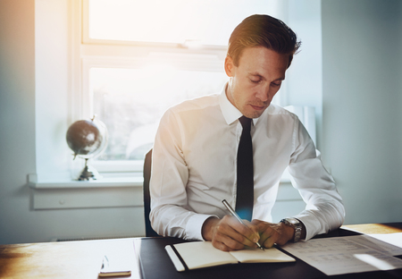 paralegal: Executive business man working at office writing in a calendar and looking seriously