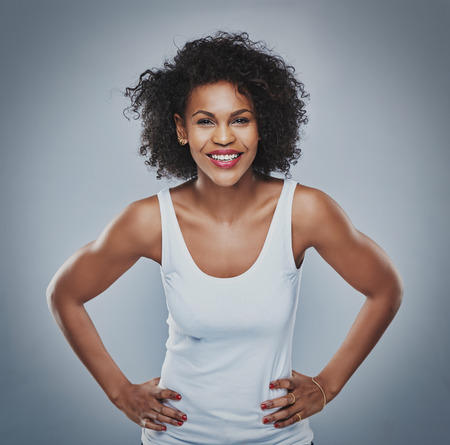 Front centered view on happy young Black female with enthusiastic expression leaning forward with hands on hips over gray background Stock Photo