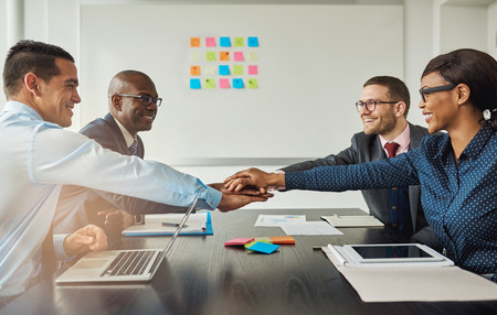 Multiracial business team signalling their commitment to each other by reaching across the table in the office to stack hands as they smile at each other