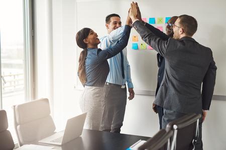 Succès diversifiée équipe commerciale multiraciale donnant un geste de cinq ans de haut, alors qu'ils célèbrent dans une salle de conférence dans un bureau Banque d'images - 57531684