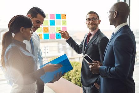 大きなガラス窓でアイデアを整理にカラフルな付箋を使用する会議の多様なビジネス人々 の若いグループ