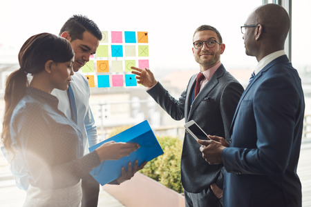 Young group of diverse business people in conference meeting using colorful sticky notes to organize ideas on large glass window