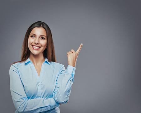 mujer de negocios joven apuntando a copyspace contra un fondo gris sonriendo
