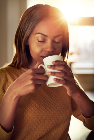tastes: Attractive young black woman drinking a cup of freshly brewed coffee smelling the aroma with her eyes closed in bliss as she relaxes indoors at home Stock Photo