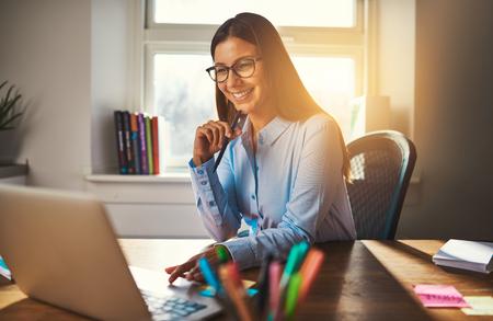 ラップトップを使用してオフィスで働いている女性を笑顔、暖かい色の太陽の光 写真素材