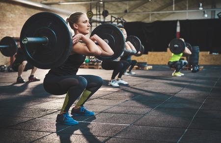 Fit jonge vrouw opheffing barbells zoek gericht, uit te werken in een sportschool met andere mensen Stockfoto