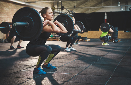 Fit young woman lifting barbells looking focused, working out in a gym with other people
