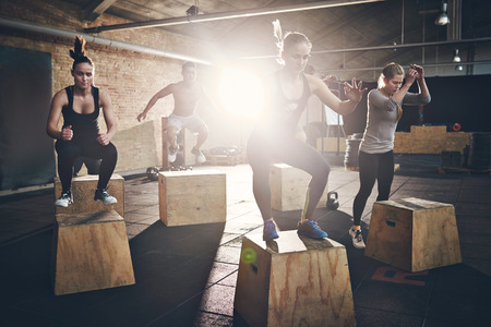 gym: Fit young people doing box jumps as a group in a gym Stock Photo