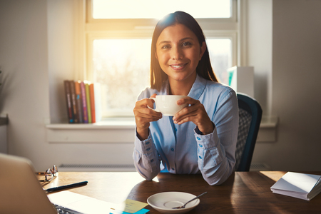 energising: Woman working at office drinking coffee smiling at camera at desk