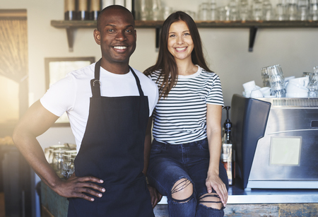 Pair of happy African and Caucasian young workers standing together in restaurant beside table