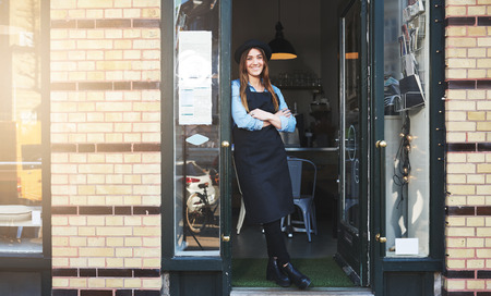 Beautiful young woman in apron and hat leaning against doorway of brick wall coffee house or restaurant as owner or employee Фото со стока