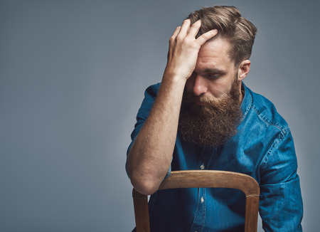 downhearted: Depressed young bearded man wearing blue denim shirt with rolled up sleeves facing back of chair and holding forehead over gray background