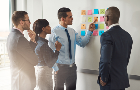 colleagues: Multiracial group of colleagues discussing a business plan standing around a set of colorful memo notes stuck on the wall