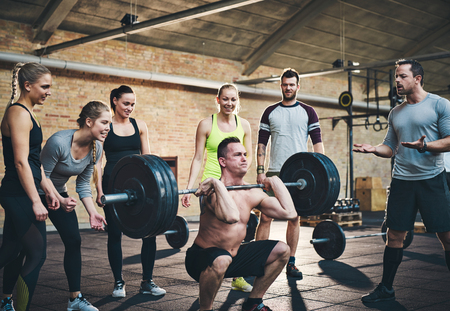 cheering people: Fit man lifting barbells looking focused, working out in a gym with other people cheering him on in support