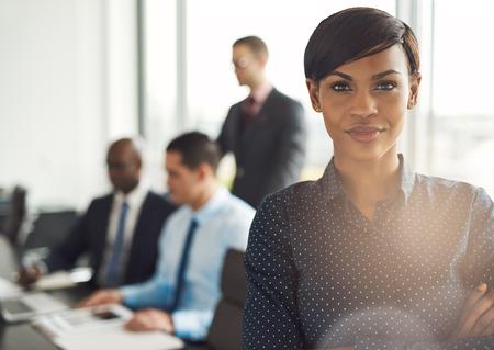 Atractiva joven dueño del negocio de mueca en la oficina con la blusa de lunares, los brazos cruzados y expresión de confianza en frente de un grupo de empleados en mesa de conferencias Foto de archivo