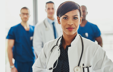 Black female doctor leading medical team at hospital, stethoscope around neck Stock Photo