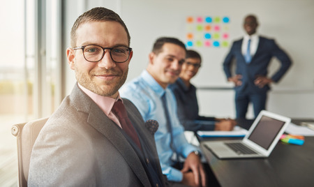 achiever: Handsome bearded man wearing suit and tie with three professional co-workers in meeting at conference table in front of a large white board